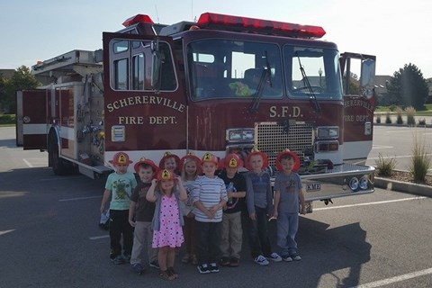 Little kids posing in front of a fire truck and wearing fireman hats