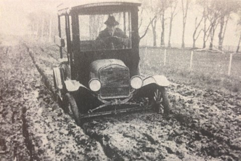A Ford Model T vehicle driving along a mud road in Schererville, prior to roads actually being paved