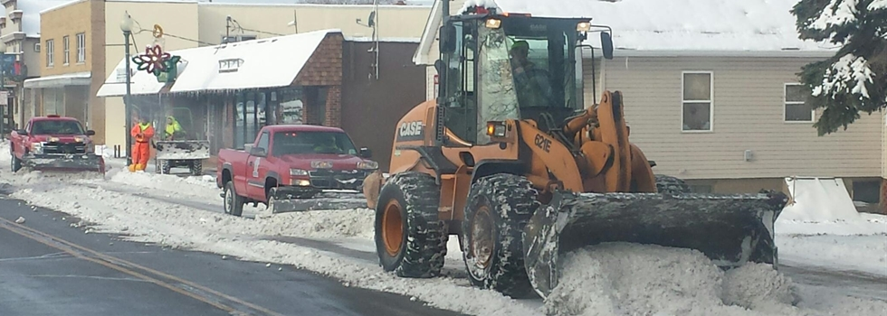 Several trucks and a front end loader plow snow off of the street in Downtown Schererville