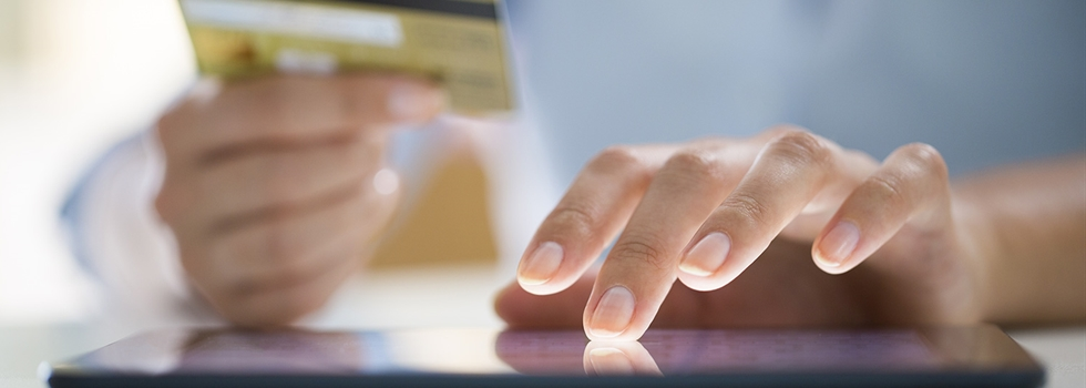 Person paying a bill online with a credit card.